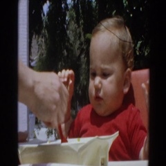 1964: little boy eating his food in his highchair. NORTH HOLLYWOOD, CALIFORNIA Stock Footage