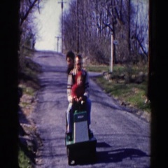 1964: family riding on a piece of equipment down a road having a great time  Stock Footage