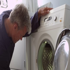 Plumber Servicing Domestic Washing Machine Shot On R3D Stock Footage