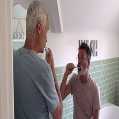 Male Homosexual Couple Brushing Teeth In Bathroom Together Stock Footage