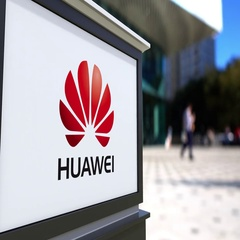 Street signage board with Huawei logo. Blurred office center and walking people Stock Footage