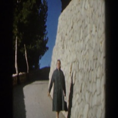 1960: woman walking by a large stonewall. ISRAEL Stock Footage