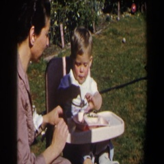 1958: baby boy in a highchair outdoors eating; mom watches showing him how to Stock Footage