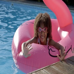 Girl Having Fun With Inflatable In Outdoor Swimming Pool Stock Footage