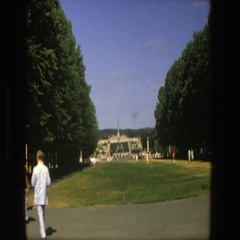 1975: men and women walk about the grounds of a garden toward a monument  Stock Footage