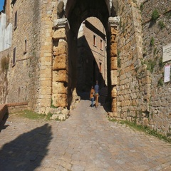 Couple walking below the Porta dell'Arco arch in Volterra Stock Footage