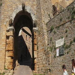 People walk below the Porta dell'Arco arch in Volterra Stock Footage