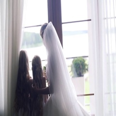 Bride with little bridesmaids at home stand by window back backlight slow motion Stock Footage