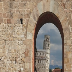Leaning tower of Pisa seen from an arch on the medieval walls Stock Footage