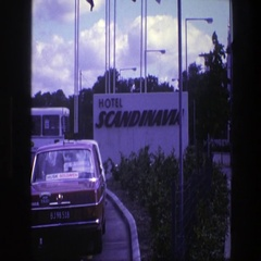 1975: waiting in traffic behind a taxi, to enter a large hotel parking lot Stock Footage
