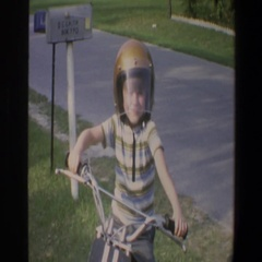 1973: young boy goes inside, then sits atop his motor scooter. MINNESOTA Stock Footage