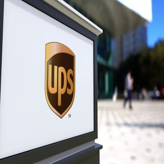 Street signage board with United Parcel Service UPS logo. Blurred office center Stock Footage