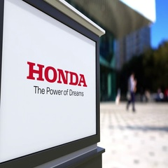 Street signage board with Honda logo. Blurred office center and walking people Stock Footage