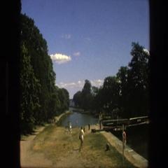 1975: a woman walking towards a large body of water next to a bridge COPENHAGEN Stock Footage