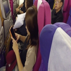 Asia girl uses phone on airplane Stock Footage