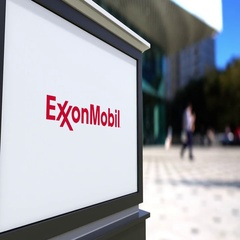 Street signage board with ExxonMobil logo. Blurred office center and walking Stock Footage