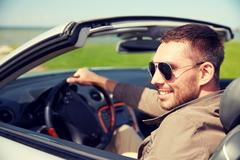 Happy man driving cabriolet car outdoors Kuvituskuvat