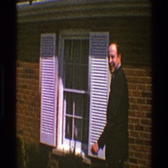 1969: a handsome man in formal dress wishing and entering a house CLARENDON Stock Footage