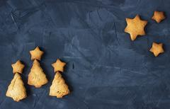 Background with baked star-shaped and christmas tree - shaped gingerbread Stock Photos