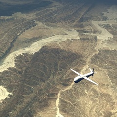 Military drone flying over desert Stock Footage