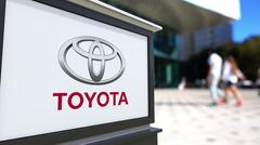 Street signage board with Toyota logo. Blurred office center and walking people Stock Illustration