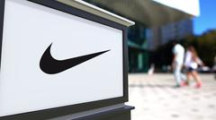 Street signage board with Nike logo. Blurred office center and walking people Stock Illustration