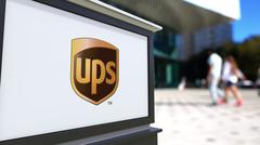 Street signage board with United Parcel Service UPS logo. Blurred office center Stock Illustration