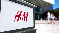 Street signage board with H&M logo. Blurred office center and walking people Piirros