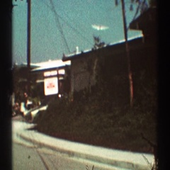 1969: a view of a car parked on a neighborhood street in a residential area  Stock Footage