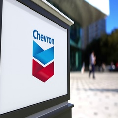 Street signage board with Chevron Corporation logo. Blurred office center and Stock Footage