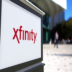 Street signage board with Xfinity logo. Blurred office center and walking people Stock Footage