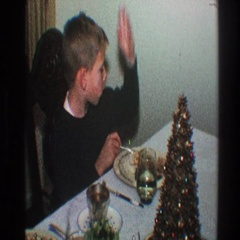 1968: little boy acting silly at the dinner table while his mom isn't catching Stock Footage