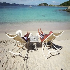 Elderly couple relaxing in beach chairs on dead man's bay, peter island Stock Footage