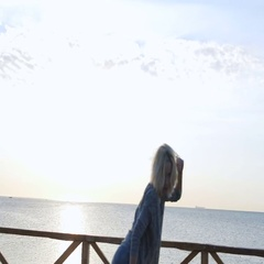 Young blond woman jumping happy near the sea at sunrise time in the summer Stock Footage
