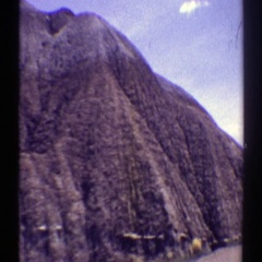 1969: a road running in the middle of a mountain with green grass and rocks Stock Footage