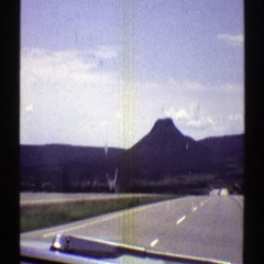 1969: car on highway driving towards a mountain ARIZONA Stock Footage
