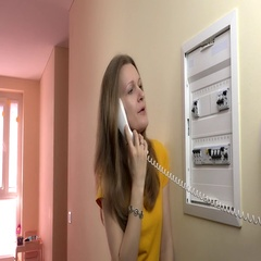 Pretty woman consult with electrician on wire phone near circuit breaker box Stock Footage