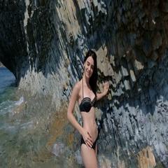 Petite girl in a black bikini relaxing on a rocky beach Stock Footage