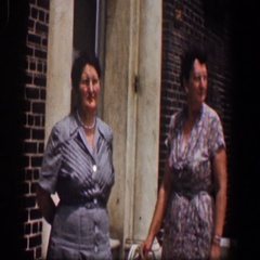 1961: two well dressed women stand in front of a building BALTIMORE MARYLAND Stock Footage