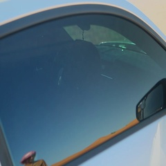 Arab man wearing sunglasses, checking his face in car window. Stock Footage