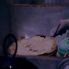 Baker preparing Arabic bread on griddle. Stock Footage