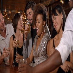Young adult friends making a toast by the bar at a party Stock Footage