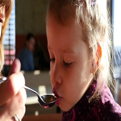 Mom feeding little child girl daughter - eating a soup from a spoon Stock Footage