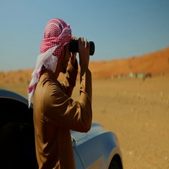 Arab man looking through binoculars. Stock Footage