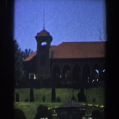 1964: a well-kept lawn, studded with trees, in front of a large building  Stock Footage