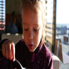 Little child girl eating a soup from a spoon in slow motion Stock Footage