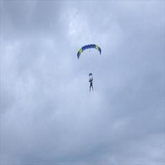 Man landing his parachute on the beach Stock Footage