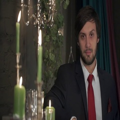 Portrait of brutal bearded man in a suit with a red tie in a romantic atmosphere Stock Footage