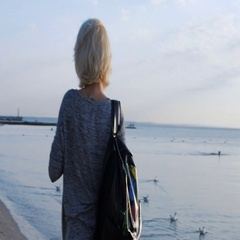 Girl with long legs walks with her colorful bag near the beach with gulls Stock Footage