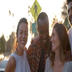 Group of smiling young adult friends embracing in the street Stock Footage